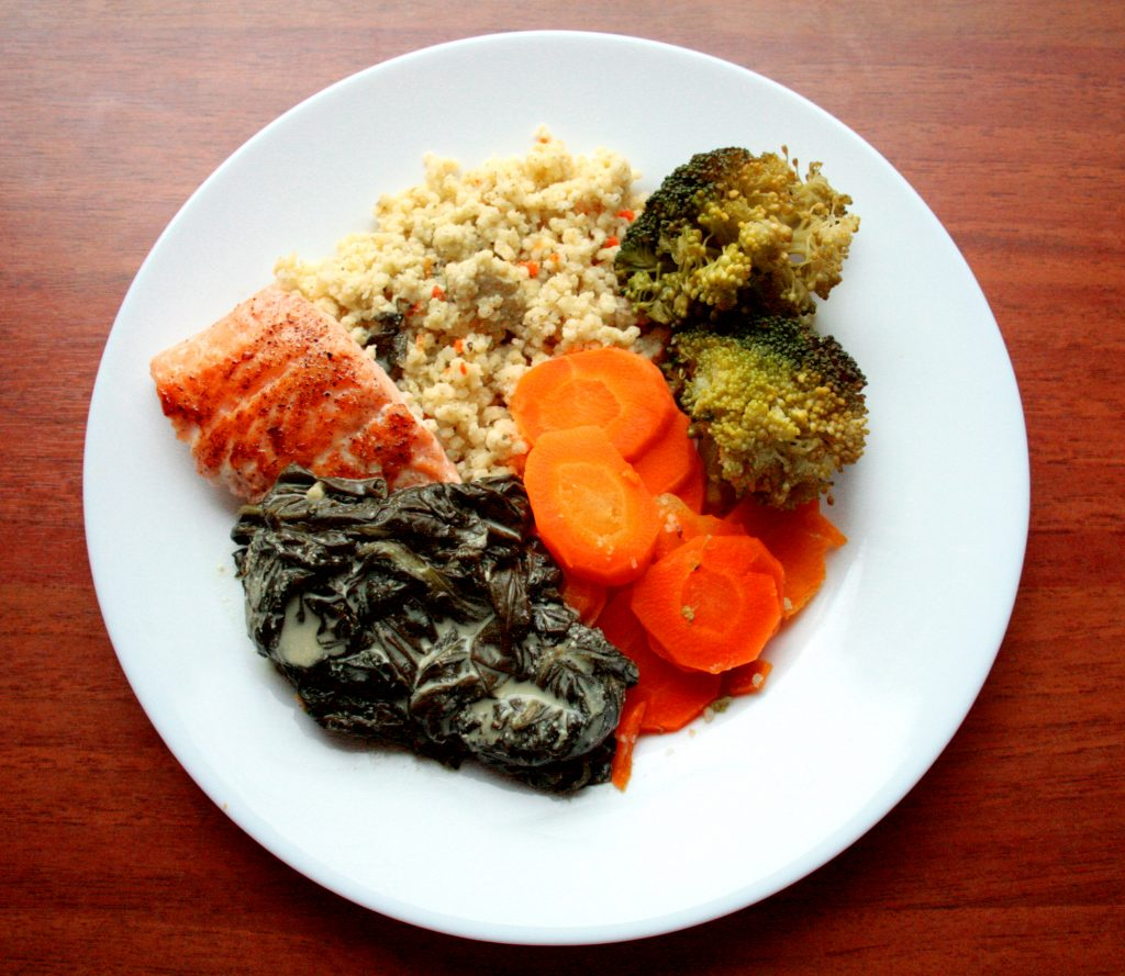 Salmon in a creamy spinach blanket, with millet and vegetables